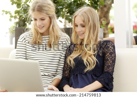 Young women sitting at coffee shop and using laptop.  City life. - stock photo