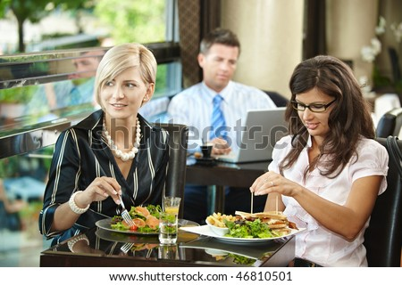 Young women sitting at table, eating sandwich and salad in restaurant, smiling. - stock photo