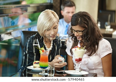 Young women sitting in cafe having sweets, looking at mobile phone. - stock photo