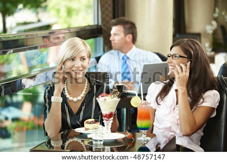 Young women sitting in cafe having sweets, talking on mobile phone. - stock photo