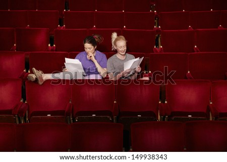 Young women sitting in theatre stall with scripts - stock photo