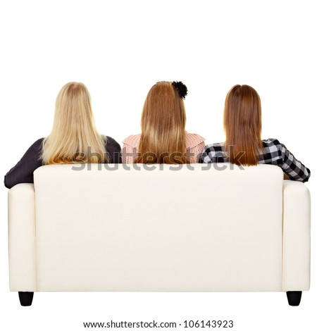 Young women sitting on sofa - rear view. Isolated on white - stock photo