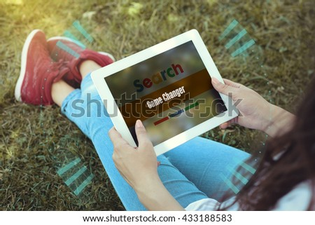 Young women sitting on the grass on a Tablet PC is searching for Game Changer. - stock photo