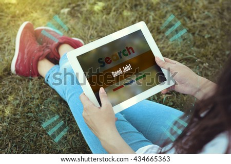 Young women sitting on the grass on a Tablet PC is searching for Good Job!. - stock photo
