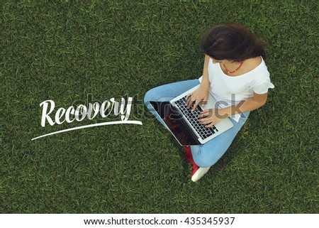 Young women sitting on the grass on a Tablet PC is searching for Recovery. - stock photo