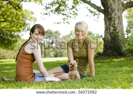 Young women sitting with dog at a park - stock photo