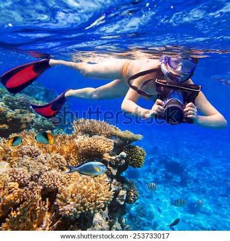 Young women snorkeling in the tropical water with camera - stock photo