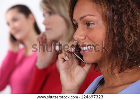 Young women using cellphones - stock photo