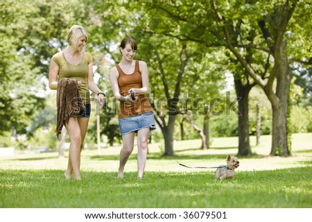 Young women walking dog at a park - stock photo
