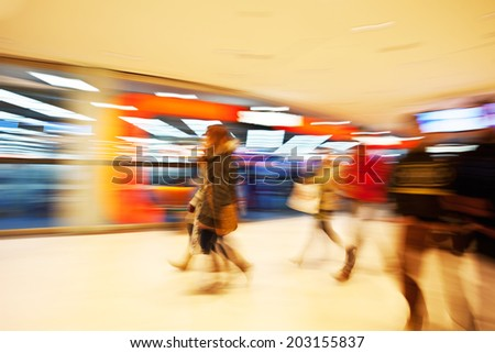 Young women walking past window display in clothes shop - stock photo