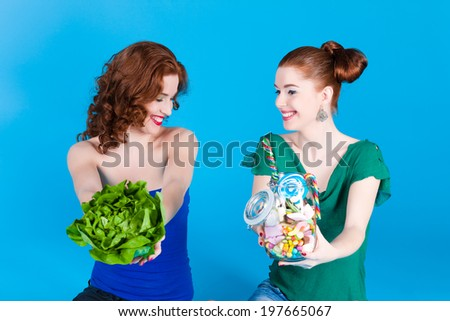 Young women with healthy and unhealthy food like salad and candy in studio - stock photo