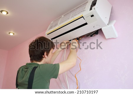 Young worker connects the wires to the new air conditioner in the living room - stock photo