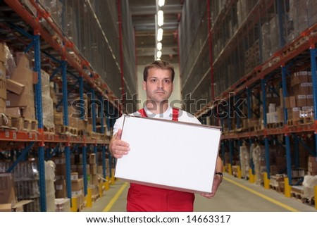 young worker in uniform carrying box in warehouse - stock photo