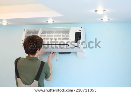 Young worker installs air conditioner in the room with blue walls - stock photo