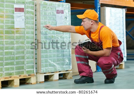 young worker man in uniform at warehouse checking rack arrangement of laminate flooring - stock photo