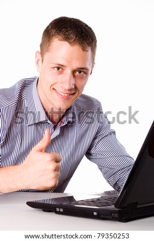 young worker sitting at table with laptop - stock photo