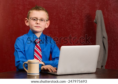 Young working boy with tie and grown up glasses on computer. - stock photo