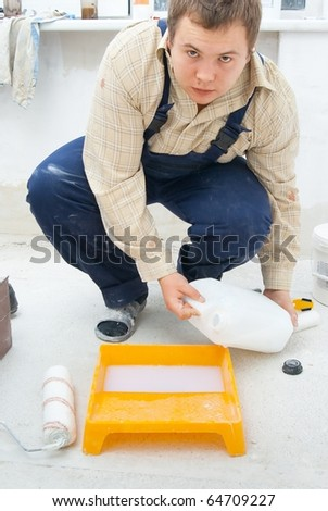 young workman pouring paint from a bucket - stock photo