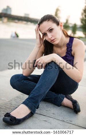 Young worried and nervous woman holding mobile phone - stock photo