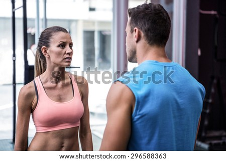 Young worried bodybuilder talking to her colleague in the crossfit gym - stock photo