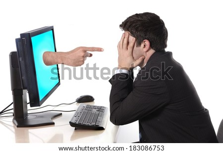 young worried business man deppressed in stress with computer hand with accusing finger pointing him in failure, crisis and financial ruin concept and social network media cybermobbing and bullying  - stock photo