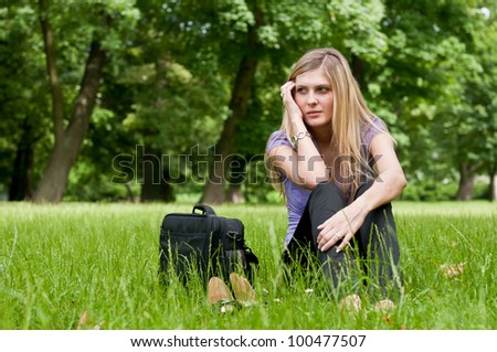 Young worried business woman siting in grass - notebook bag and shoes lying next - stock photo