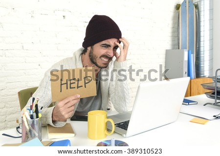 young worried businessman in cool hipster beanie look holding help sign working in stress at home office with computer laptop in business frustration overworked and deadline project - stock photo