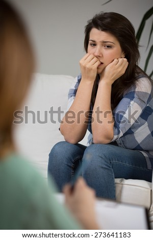 Young worried female patient at psychologist's cabinet - stock photo