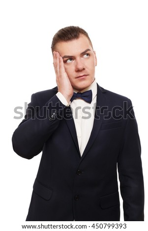 Young worried man in black suit with bow tie isolated at white background. Portrait of guy pensive, looking upset and unhappy. Male problems and issues - stock photo