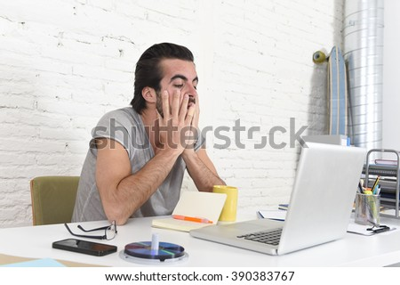 young worried student or businessman at laptop covering his face with his hands depressed and sad suffering stress for exam or deadline over business project sitting at modern home office - stock photo