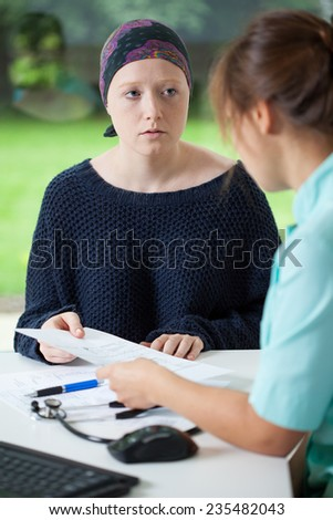 Young worried woman with cancer and her female doctor - stock photo