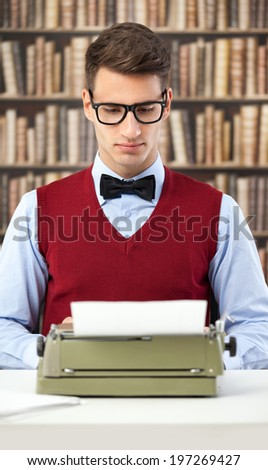 Young writer typing on typewriter in library - stock photo