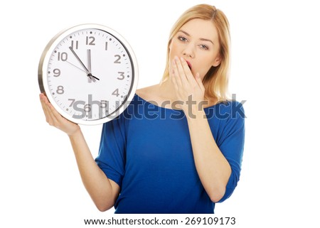 Young yawning woman holding a clock.  - stock photo