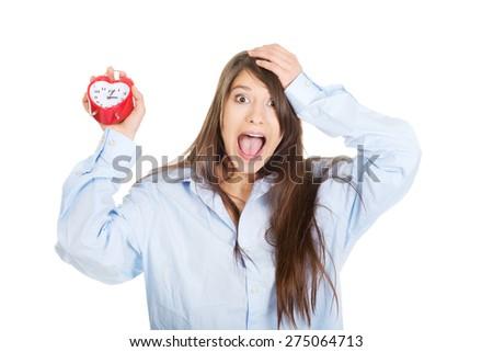 Young yawning woman in big shirt holding alarm clock. - stock photo