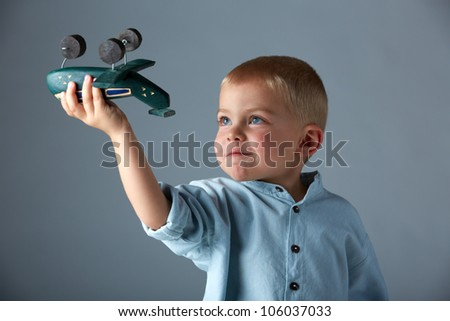 young 3 year old boy wearing blue shirt playing with wooden toy airplane in his hand on blue studio background. - stock photo