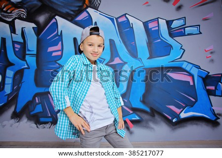 young 10-years boy posing in front of a colorful graffiti wall. Teenager boy dancing hip hop over textured background - stock photo