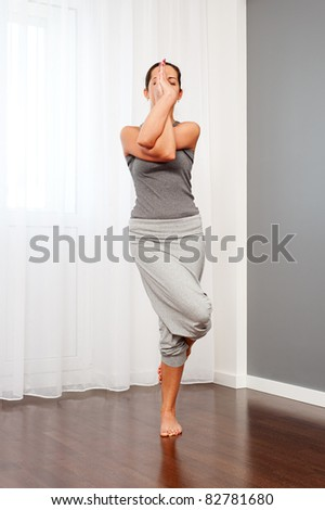 young yoga female doing yogatic exercise at home - stock photo