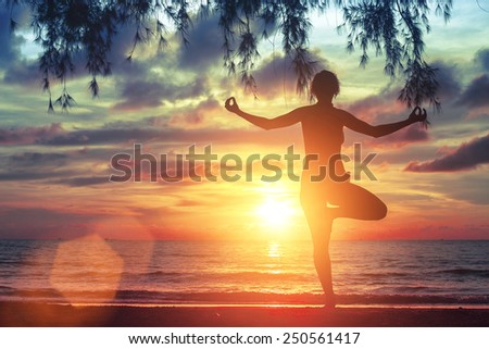 Young yoga girl practicing on the ocean beach at amazing beautiful sunset. - stock photo