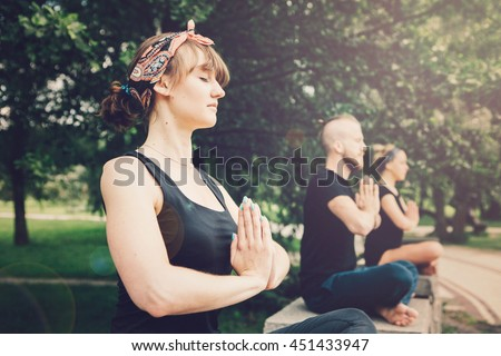 Young yoga practitioners in group doing yoga on nature. - stock photo