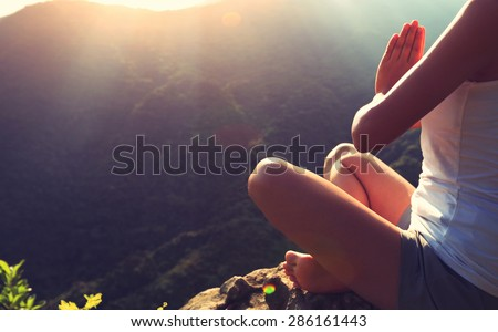 young yoga woman at sunrise mountain peak - stock photo