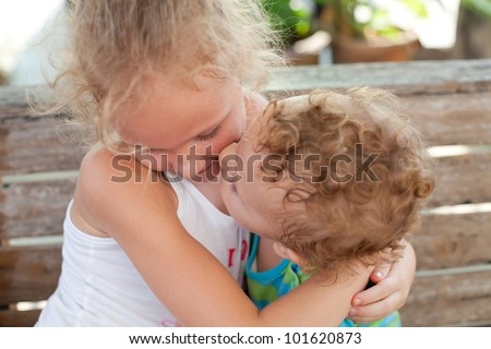 younger brother kisses the cheek of his older sister - stock photo