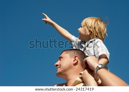 younger brother younger on shoulders at senior brother against the sky - stock photo