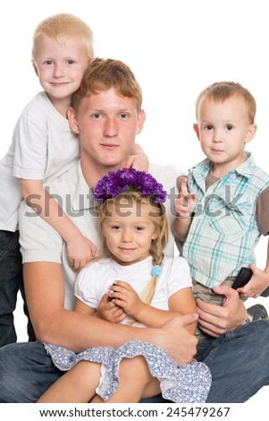 Younger brothers and sister with big brother sitting on the carpet, isolated on white - stock photo