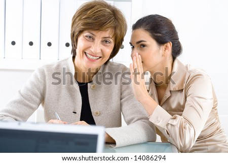 Younger businesswoman whispering to a smiling senior businesswoman at office. - stock photo
