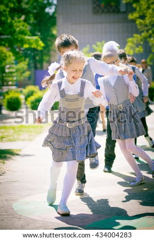 Younger students in the form school children playing outdoors, playing hopscotch on playground outdoors, children outdoor activities. happy kids group have fun outdoors. motion blur - stock photo