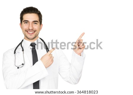 Your ad here. Handsome male doctor smiling happily pointing at the copyspace on the side isolated on white  - stock photo
