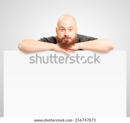 Your advertising below. Handsome young man with long beard in casual wear leaning at copy space and smiling while standing against white background - stock photo