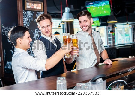 Your health. Four friends men drinking beer and having fun together in the bar - stock photo