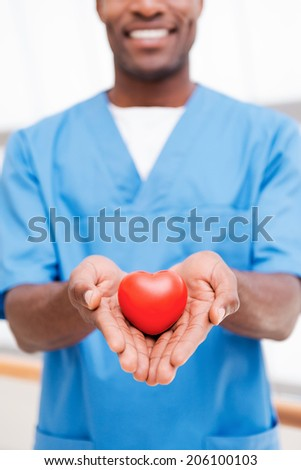 Your heart in right hands. Close-up of confident young African doctor in blue uniform holding heart prop in his hand and smiling - stock photo