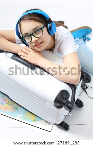 Your journey of dreams. Girl in blue headphones packed suitcase with things for a holiday trip  - stock photo